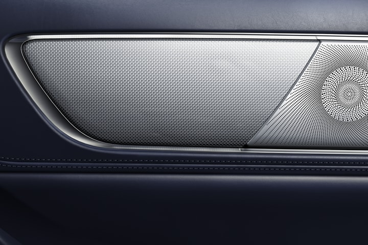 A close up image shows the fine detail work of a speaker cover in a Lincoln Black Label Continental in the rhapsody theme