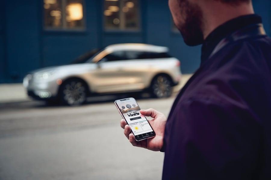 Una mujer interactúa con la aplicación Lincoln Way de su smartphone mientras se acerca a su Lincoln Corsair